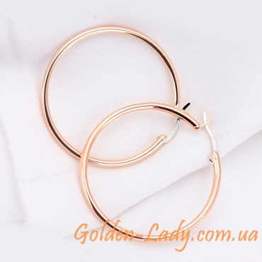 золотые сережки в виде колец лежат