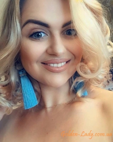 Голубые серьги кисти на ухе блондинки